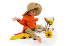 One little girl arranging flowers sitting. One little girl wearing big hat and orange blouse arranging flowers (Helianthus) in vase Stock Images