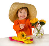 One little girl arranging flowers on the table. One little girl wearing big hat and orange blouse arranging flowers (Helianthus) in vase Stock Photos