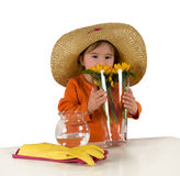 One little girl arranging flowers on the table. One little girl wearing big hat and orange blouse arranging flowers (Helianthus) in vase Royalty Free Stock Images