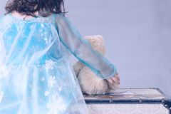 One little girl dressed as a princess holds a teddy bear while sitting on a chest. A little girl dressed as a princess holds a teddy bear while sitting on a Royalty Free Stock Photography