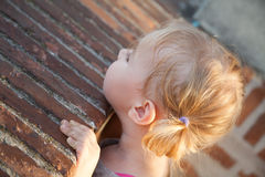 One little girl looking out over stone brick wall Royalty Free Stock Photos