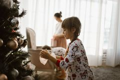 One little girl in pajama decorates a New Year`s tree in the light cozy room royalty free stock photos
