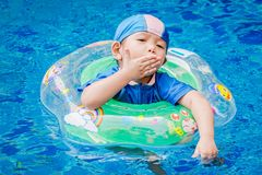 One little girls swimming in the pool with rubber ring. One little girls swimming in the pool with rubber ring, having fun in swimming pool royalty free stock photo