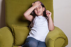 One little middle eastern beautiful small girl sitting feeling bad. She feels cold Royalty Free Stock Image