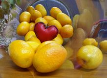 One  little red heart on small oranges in glass bottle  on wooden floor Royalty Free Stock Images