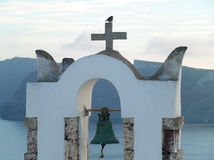 One little sparrow perching on the cross of a white church bell tower before sunset, Santorini island. Greece Royalty Free Stock Photos