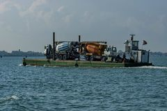 One load flat-boat ferry two concrete mixer truck. Via the lagoon, Italy stock photography