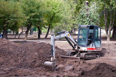 Excavator construction machinery. One Loader excavator construction machinery with green tree Stock Photos