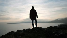 One lonely man looking at the sunset reflection. One lonely hiker at wild area with stone mount and coast. Seaside and good feelings, emotional concept of life stock video footage