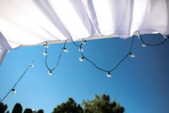 One long electric garland for lighting with white light bulbs against the background of a blue clear sky. Bokeh..Decorative. One long electric garland for stock images