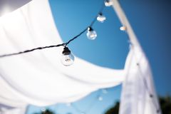One long electric garland for lighting with white light bulbs against the background of a blue clear sky. Bokeh..Decorative