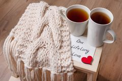 Couple of cups, background warm scarf, in home interior, napkin with text. stock photo