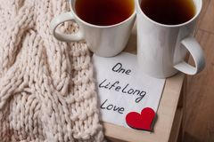 One long life of love is an abstract symbolic image. Couple of cups, background warm scarf, in home interior, napkin with text.  Stock Photography