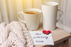 One long life of love is an abstract symbolic image. Couple of cups, background warm scarf, in home interior, napkin with text Stock Image