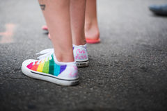 One Love. A crowd member wears striped rainbow shoes in the Gay Pride Parade - Des Moines, 2015 stock photography
