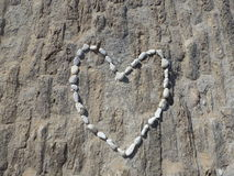 One love. Heart made of beach pebbles stock photography