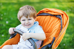 One lovely caucasian toddler boy of two years sitting in pram on Stock Image