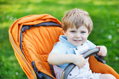 One lovely caucasian toddler boy of two years sitting in pram on. Summer day, Europe, Germany, outdoors Royalty Free Stock Photography