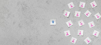 One male figure againts lots of female. Male discrimination, feminism. One man against many women, gender figures on paper cards, gray background, panorama, copy royalty free stock photography