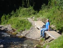 One male hiker rests enjoying the sunshine on his face. He sits on a small wooden bridge next to the Lech river. The trail is the first stage of the Lech Stock Images