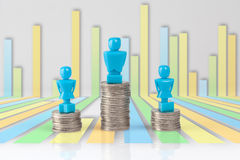 One male and two female figurines standing on piles of coins. Stock Photos