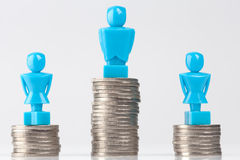 One male and two female figurines standing on piles of coins Stock Photo