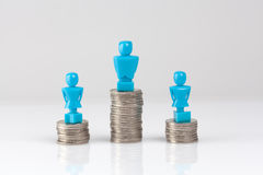 One male and two female figurines standing on piles of coins. Stock Photo