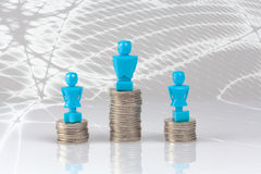 One male and two female figurines standing on piles of coins. Royalty Free Stock Images