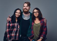 One male and two women. Bearded male with tattoos on his body and two brunette hipster women isolated over grey background Stock Photo