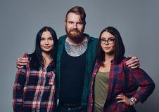 One male and two women. Bearded male with tattoos on his body and two brunette hipster women isolated over grey background Stock Photography