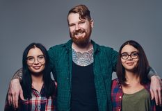 One male and two women. Bearded male with tattoos on his body and two brunette hipster women isolated over grey background Stock Image