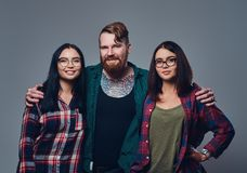 One male and two women. Bearded male with tattoos on his body and two brunette hipster women isolated over grey background Stock Images