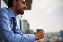 One male worker drinking coffee on office balcony. Corporate time-out. Close up low angle portrait of young businessman standing on office balcony while having royalty free stock images