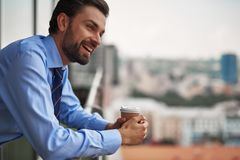 One male worker drinking coffee on office balcony stock photo