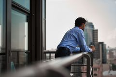 One male worker drinking coffee on office balcony. Corporate time-out culture. Back side portrait of young businessman standing on office balcony with cup of royalty free stock images