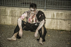 One male zombie sitting in empty city street on Stock Photo