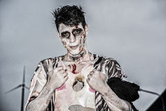 One male zombie standing in empty city street on. One male zombie standing in empty city street at night looking at camera. Halloween theme Royalty Free Stock Images