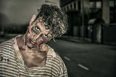 One male zombie standing in empty city street on. One male zombie standing in empty city street at night looking at camera. Halloween theme Stock Photography