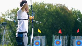 One man aims at a target, shooting a bow. 4K stock footage