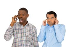 One man annoyed with another who talks loudly over the phone Royalty Free Stock Images