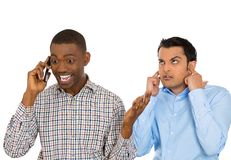One man annoyed with another who talks loudly over the phone Royalty Free Stock Image