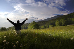 One man with arms outstretched in alpine landscape Stock Image