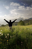 One man with arms outstretched in alpine landscape Royalty Free Stock Photo