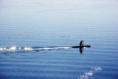 One man with canoe on lake. A silhouette of a canoe rower practicing on lake Royalty Free Stock Photography