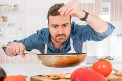 One man is cooking in his kitchen and adding salt royalty free stock image