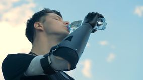 Cyborg with bionic arm drinks water from a bottle, using his robotic prosthesis. One man drinks water from a bottle, using his robotic prosthesis