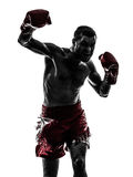 One man exercising thai boxing silhouette. One caucasian man exercising thai boxing in silhouette studio  on white background Royalty Free Stock Images