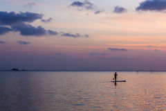 One man floating in the water on the background of beautiful sunset Royalty Free Stock Photos