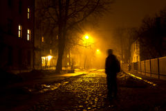 One man on the foggy street at night. Portrait of a man standing in the middle of the street at foggy night. Silhouette of a man. Light on background Royalty Free Stock Photography