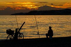 Man  silhouetted against a glorious sunset  sits waiting with his fishing rods.